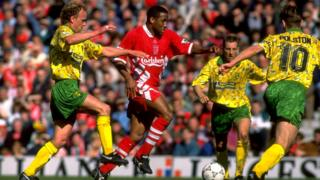 John Barnes surrounded by Norwich players in a terrible kit