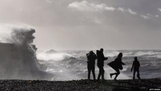 Braving the weather, members of the public in Dover watch large waves produced by the storm break against the harbour wall.