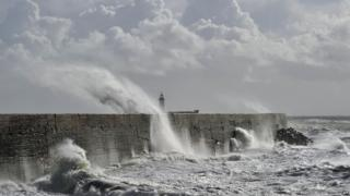 Waves crashing over the harbour in Newhaven, east Sussex.