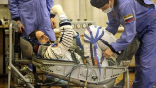 Astronaut in spacesuit getting strapped into position
