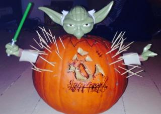 carved pumpkin with yoda model inside
