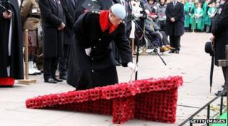 Prince Harry lays a Cross of Remembrance at the visit