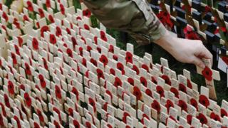 A soldier places a cross in a field of similar crosses, each have poppies on them