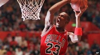 Michael Jordan slams a basketball into a net