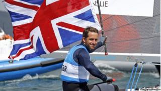 Ben Ainslee holding the British flag on a sailing boat
