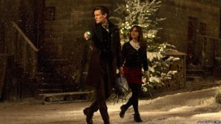 Matt Smith as the Doctor with Jenna Coleman as Clara. The Doctor is carrying a Cyberman's head.