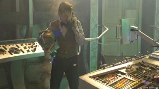 The Doctor in the Tardis holding a Cyberman's head?