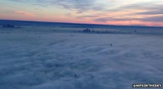 pink sky above thick clouds of fog