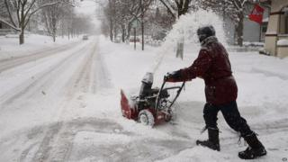 Kevin Pokorny works on his third house clearing snow for neighbour's in Barrington, Ill., Thursday, Jan. 2, 2014.