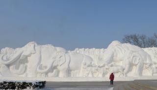 A giant snow sculpture shows elephants in a line