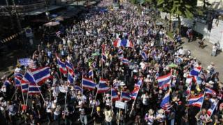 Protesters waving flags block a road in Bangkok