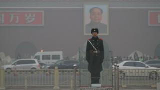 A Chinese policeman stands surrounded by thick smog in Beijing