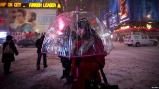 woman carrying an umbrella walks along 7th Avenue at Times Square during a snow storm in New York January 21, 2014. A