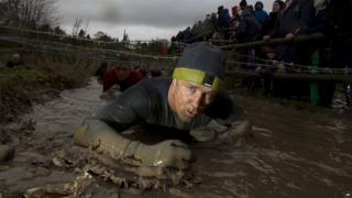 Tough Guy competitor crawls under barbed wire