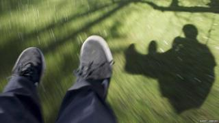 shadow of a boy on a swing on grass