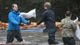 The Princes help move sandbags