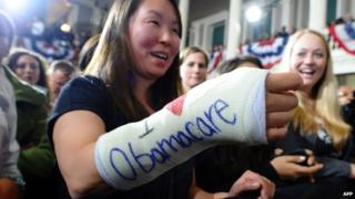 """Cathey Park shows her bandaged hand written """"I love Obamacare"""" as she waits to hear US President Barack Obama speak at the Faneuil Hall in Boston, Massachusetts, on 30 October 2013"""