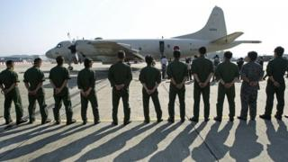 soldiers stand in a line as people board a plane