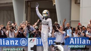 Mercedes driver Lewis Hamilton of Britain stands on his car.