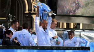 Vincent Kompany holding trophy on top of bus