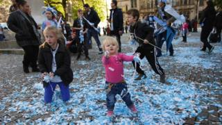 Fans playing with blue and white confetti
