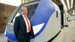 "Bombardier Transportation in France head Jean Berge stands in front of a giant model of the ""Regio 2N"" regional double-deck train developed for the French SNCF railway network"