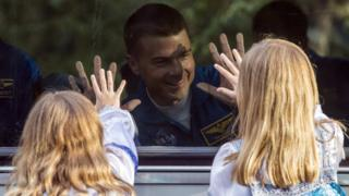 US Astronaut Reid Wiseman waves to his daughters through the window of the bus as he heads to base for final pre-flight preparations.
