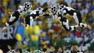 Dancers dressed as footballs leaping into the air