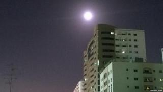 A bright moon is captured above a high rise building.