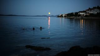 The yellow moon is hanging above the sea, being reflected in the water, near to land.