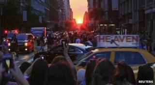 "People take pictures at sunset during the bi-annual occurrence ""Manhattanhenge"" in New York"