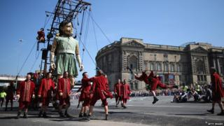 A giant marionette girl walks through Liverpool