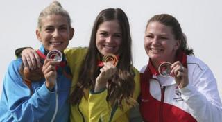 Medallists in the shooting hold their medals up