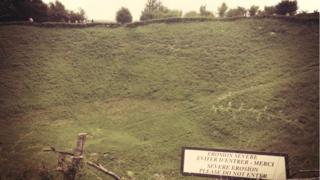 A large crater in the ground, now covered in grass so looks like a hill