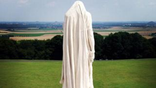 A tall white statue has its head bowed and faces away towards the fields