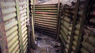 A corrugated metal trench with a muddy floor