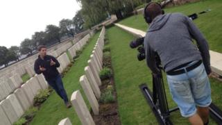 Ricky speaks to the camera as he walks through a row of gravestones