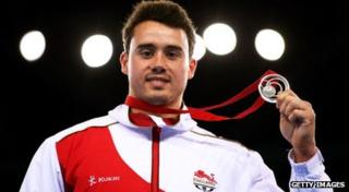 Kristian Thomas holds up his silver medal