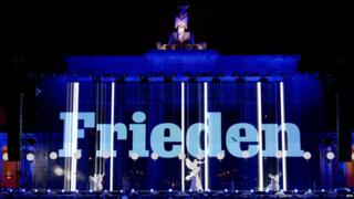 The word peace projected on the Brandenburg Gate.