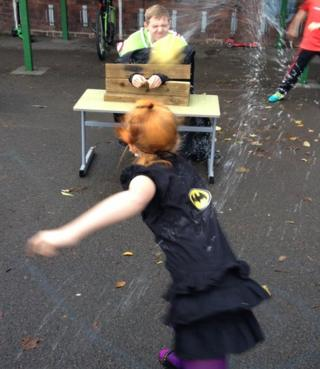 A teacher is splashed with a wet sponge