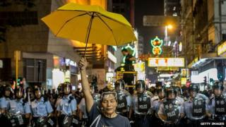 Hong Kong protester stands in front of police