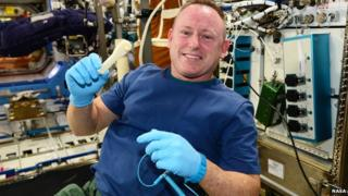 Commander Barry Wilmore on board the International Space Station, holding a 3D-printed ratchet
