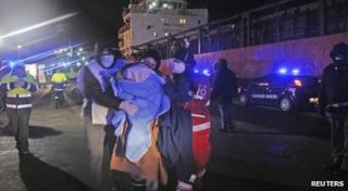 Medics help migrants after they arrived onboard the Blue Sky M cargo ship at the Gallipoli harbour southern Italy, on 31 December 2014.