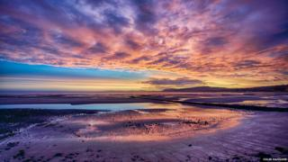 A brightly coloured sunset over a beach at low tide. The sky is lit up with colours of purple, red, yellow and blue.