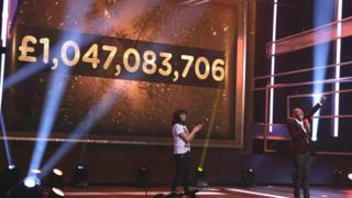 Video screen displaying Comic Relief fundraising total of 1,047,083,706 pounds.