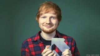 Ed Sheeran holding an award from the Official Charts Company