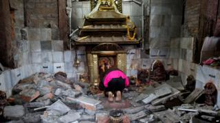 A woman prays at a shrine in a destroyed temple