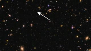 A tiny speck among larger galaxies shows the location of EGS-zs8-1.