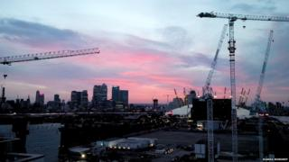 London's Canary Wharf at sunset. Greenwich landmarks and some large cranes can also been seen