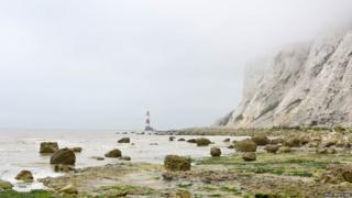 A beach scene. A lighthouse can be seen in the distance. In the background heavy fog obscures some of the cliff. The sea is choppy